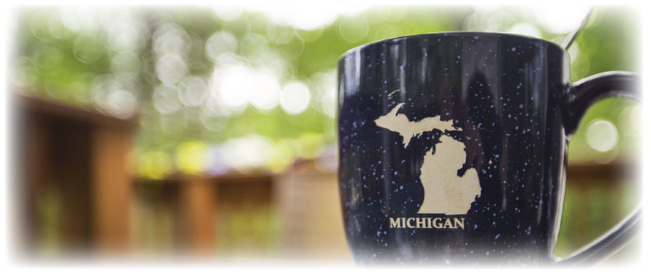blue mug with beige Michigan mitten map with green trees in background